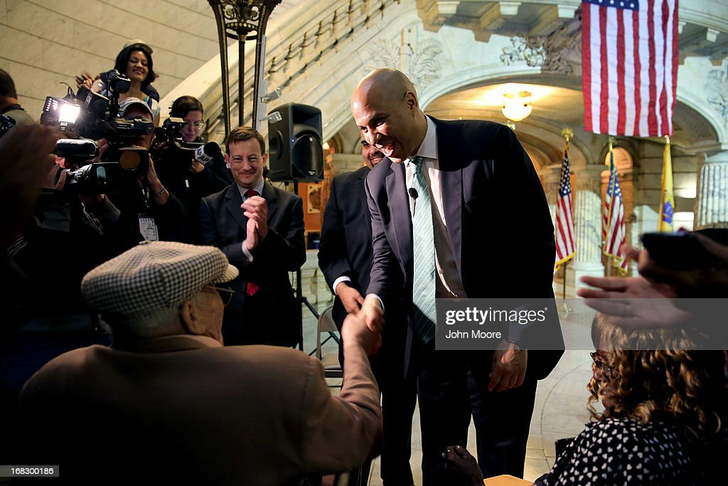 Newark Mayor Cory Booker shakes the hand of 90-year-old WWII veteran Willie Wilkins at the Newark City Hall on May 8, 2013 in Newark, New Jersey. Booker, who has declared that he will run for New Jersey's open U.S. Senate seat in 2014, honored the 90-year-old WWII veteran on the 68th anniversary of Victory in Europe Day. At the ceremony, Wilkins received his dog tags, which were recently unearthed in a French garden, some 67 years after he lost them in France during WWII.