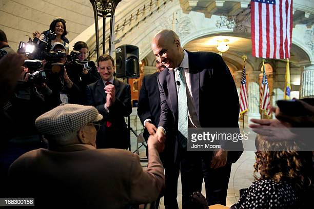 Newark Mayor Cory Booker shakes the hand of 90yearold WWII veteran Willie Wilkins at the Newark City Hall on May 8 2013 in Newark New Jersey Booker...