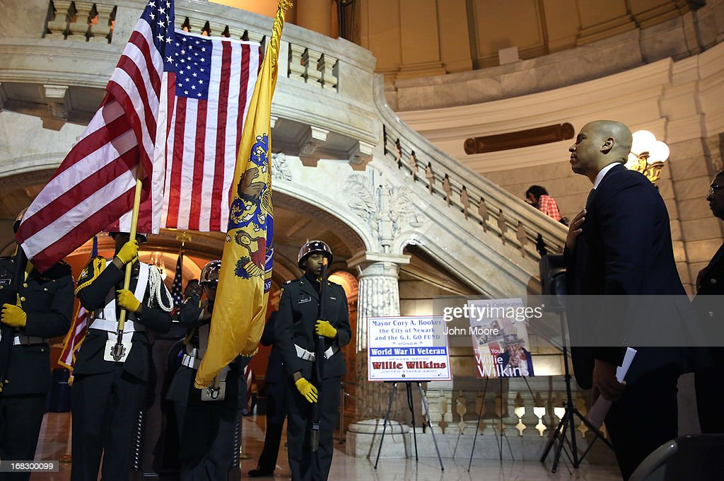 Newark Mayor Cory Booker stands for the presentation of the colors at the Newark City Hall on May 8, 2013 in Newark, New Jersey. Booker, who has declared that he will run for New Jersey's open U.S. Senate seat in 2014, was attending a ceremony honoring 90-year-old WWII veteran Willie Wilkins on the 68th anniversary of Victory in Europe Day.