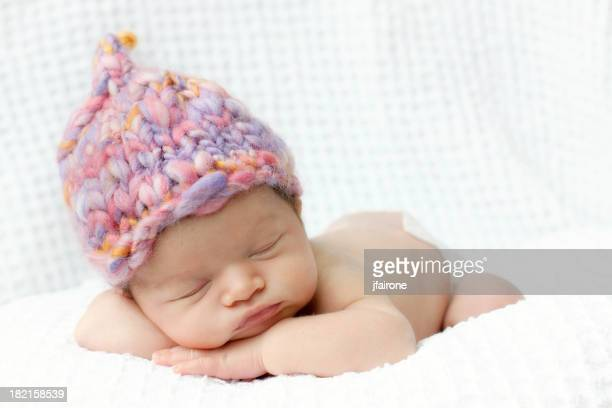 Newborn baby asleep with pink hand knit hat