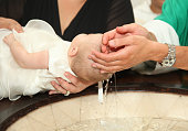 Newborn baby baptism by water with hands of priest
