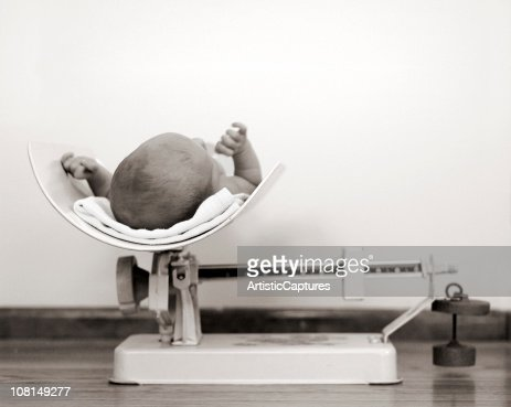 Newborn Baby Being Weighed on Vintage Scale, Black and White : Stock Photo