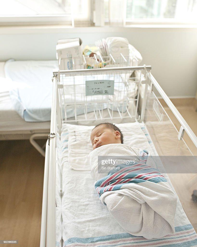 Newborn baby boy asleep in hospital bassinet : Stock Photo