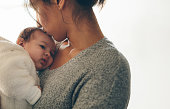 Woman carrying her newborn son and kissing on his forehead. Cute little boy in his mother's arms.