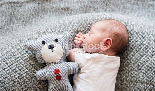 Newborn baby boy lying on bed with teddy bear, sleeping : Stock Photo