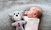 Cute little newborn baby boy lying on bed with his teddy bear, sleeping, close up