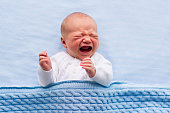 Newborn crying baby boy. New born child tired and hungry in bed under blue knitted blanket. Children cry. Bedding for kids. Infant screaming. Healthy little kid shortly after birth. Cable knit textile