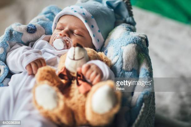 Newborn baby boy sleeping in cozy basket