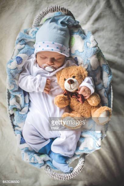 Newborn baby boy sleeping in cozy basket