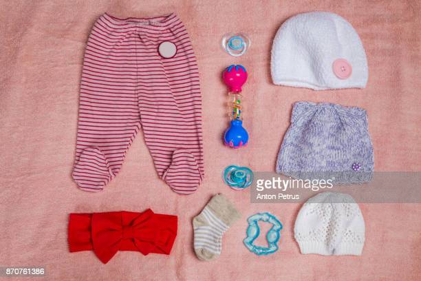 Newborn baby (girl) clothes on blue background. Knolling style.