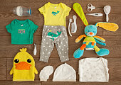 Essential accessories of a newborn infant, shot from above in a tabletop flat lay arrangement on brown wooden surface.