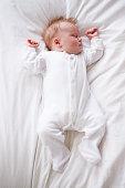 Newborn Baby Girl Sleeping In Bed