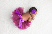Portrait of a one month old, sleeping, newborn, baby girl. She is wearing a purple tutu and sleeping on a white blanket.