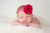 A portrait of a beautiful newborn baby girl wearing a hot pink flower headband. She is sleeping on a cream colored sheepskin rug.