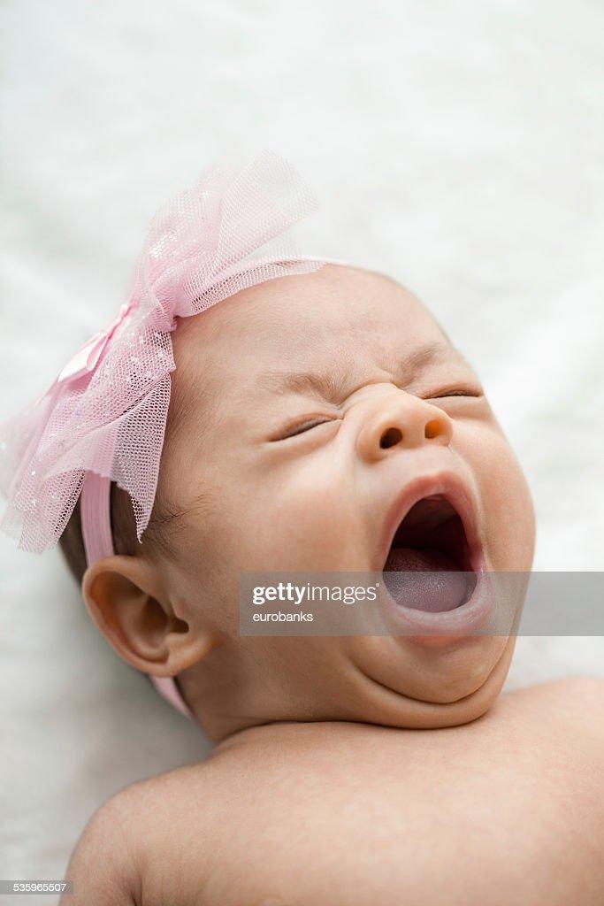 Newborn baby girl yawning : Stock Photo