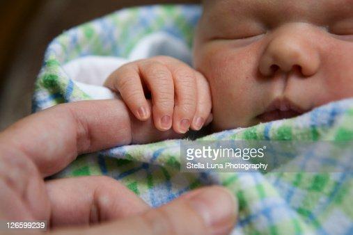 Newborn baby grasping finger