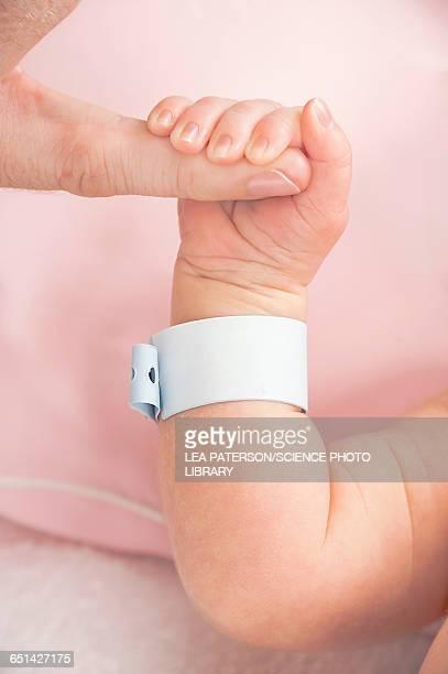 Newborn baby gripping parents finger