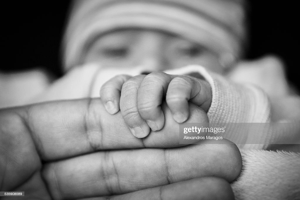 Newborn baby holding father's hand : Stock Photo