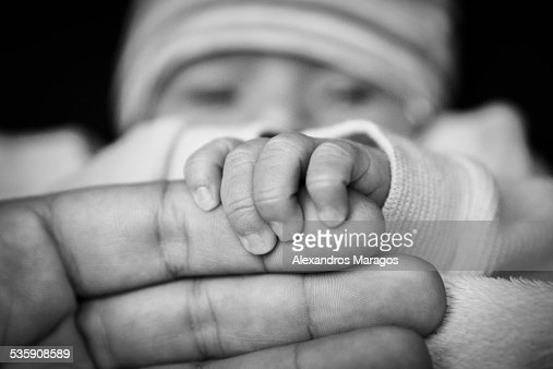 Newborn baby holding father's hand : Foto de stock