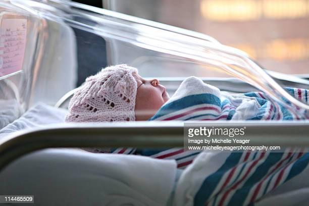 Newborn baby in hospital bassinet.