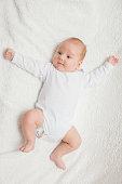 Newborn baby in white romper on white textile background