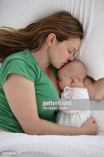 A newborn baby is cuddled by her mother while asleep Photo Tim Clayton
