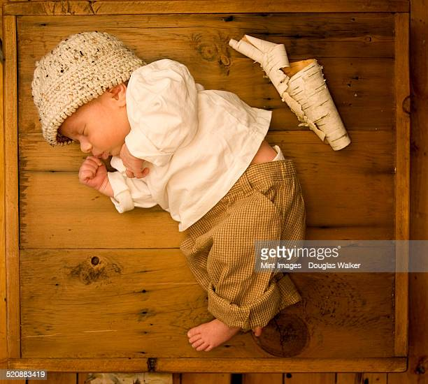 A newborn baby lying asleep on his side in a wooden box, with a scroll of white tree bark beside him.