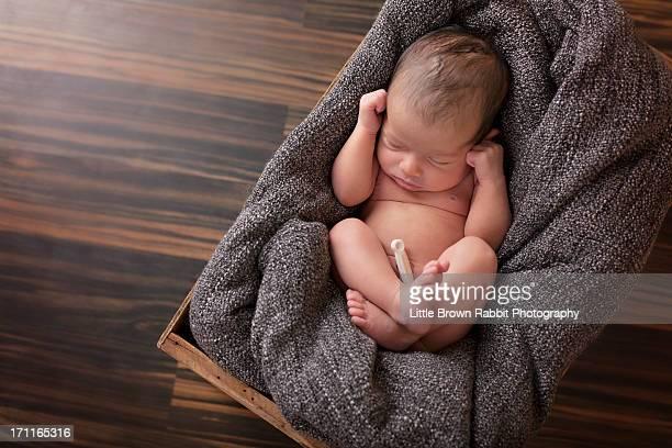 Newborn baby on a grey blanket in wooden box