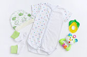 newborn baby set of clothes: patterned bodysuit with hat, knitwear booties and teether on white background