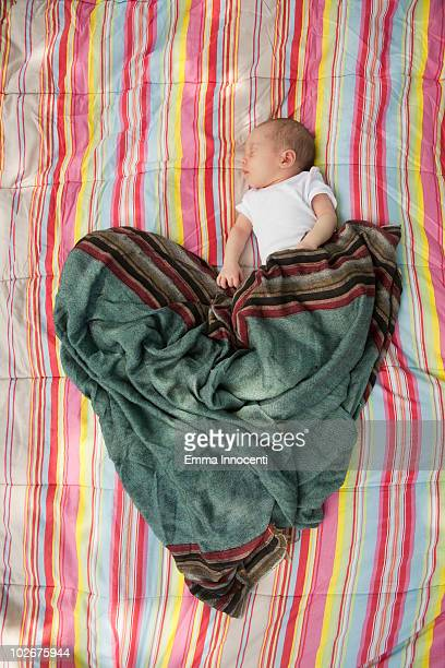 Newborn baby sleeping in heart shaped blanket