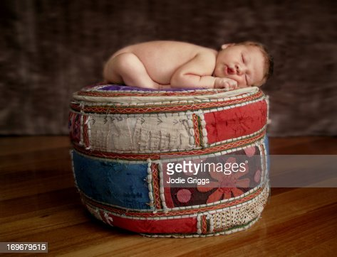 Newborn baby sleeping on colourful footrest : Stock Photo