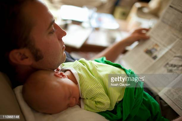Newborn baby sleeping on father, selective focus.