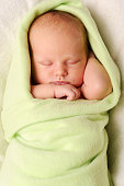 Newborn Baby Sleeping Perfectly Wrapped in Green Blanket