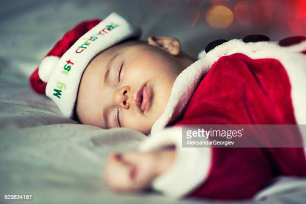 Newborn Baby Sleeping with Santa Clothes for his First Christmas