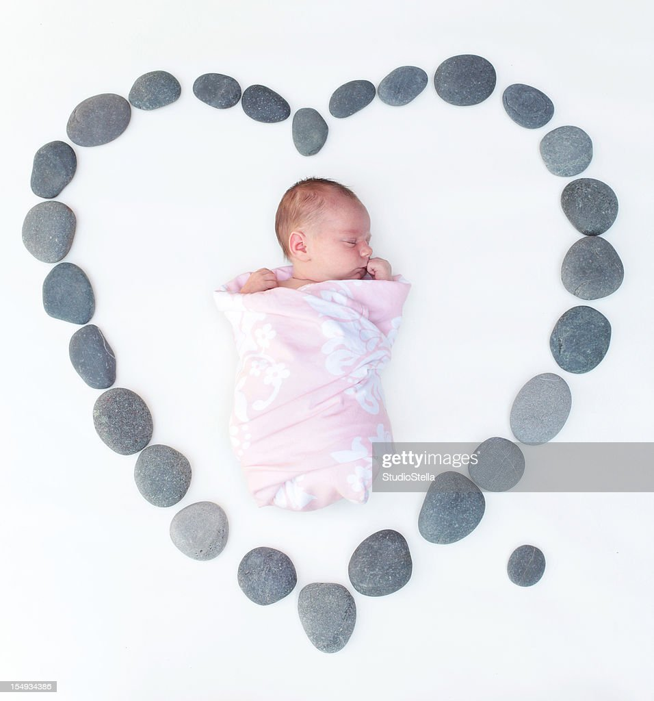 Newborn in Heart of Smooth River Stones : Stock Photo