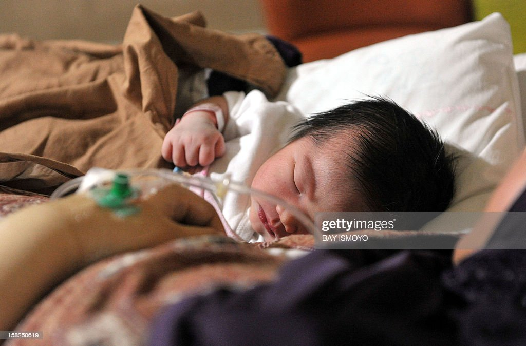 A newborn Indonesian baby girl named Malika Ifrania Altha Meara is placed next to her mother Melinda Irmayanti at the Bunda Hospital in Jakarta, where 12 lucky babies were born by C-section on December 12, 2012. Several hospitals in Indonesia's main cities performed more Caesarians than usual with new mothers hoping a 12-12-12 birth date will bring luck to their newborns.