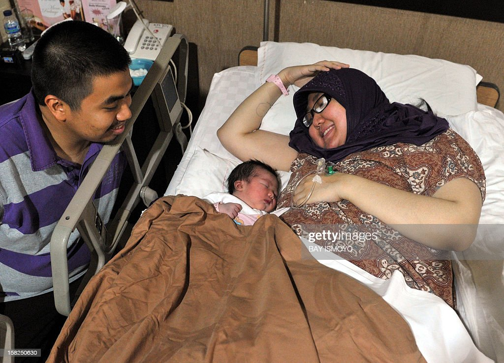 A newborn Indonesian baby girl named Malika Ifrania Altha Meara (C) is placed next to her mother Melinda Irmayanti (R) as her father Muhammad Iqbal (L) looks on at the Bunda Hospital in Jakarta, where 12 lucky babies were born by C-section on December 12, 2012. Several hospitals in Indonesia's main cities performed more Caesarians than usual with new mothers hoping a 12-12-12 birth date will bring luck to their newborns. AFP PHOTO / BAY ISMOYO