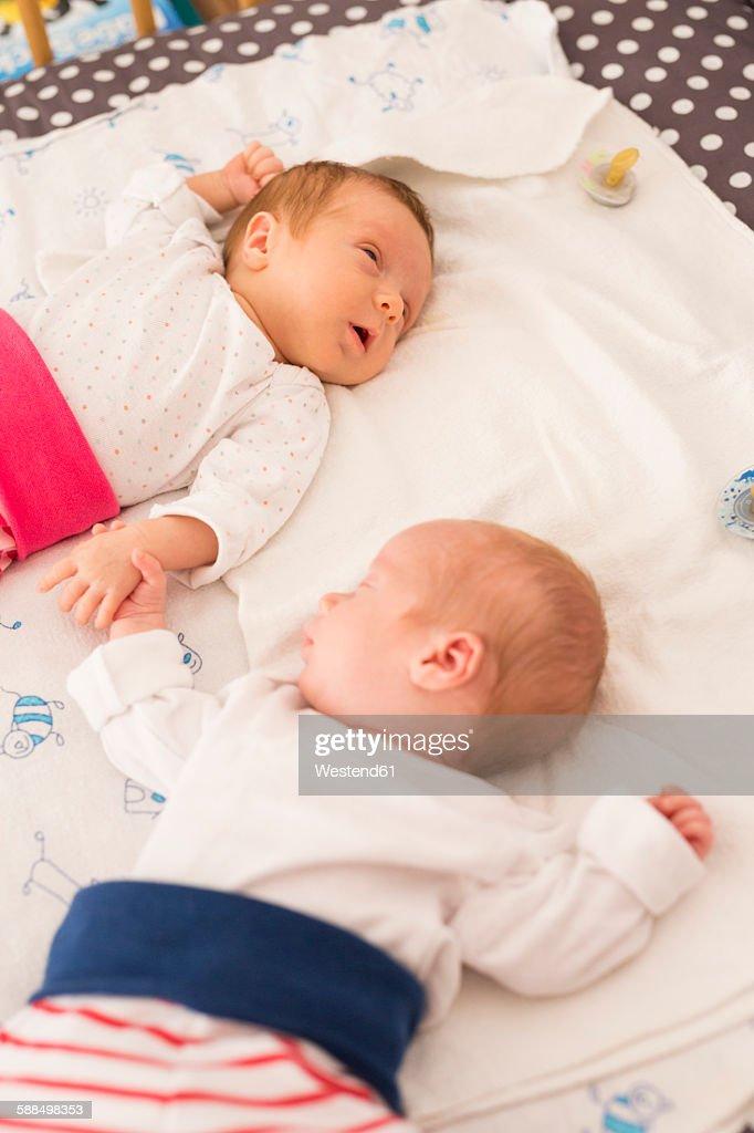 Newborn twins sleeping hand in hand : Stock Photo