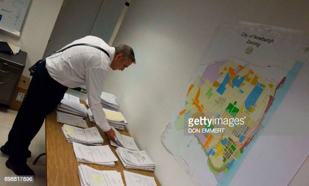Newburgh New York Assistant Fire Chief William Horton looks through a stack of building permit requests in his office on May 30 2017 Rows of...