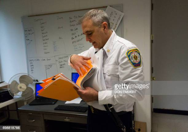 Newburgh New York Assistant Fire Chief William Horton looks through a stack of building permit requests in his office May 30 2017 in Newburgh NY Rows...