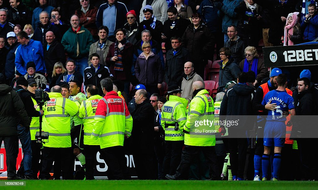 Newcastle coach John Carver (left, white top) is involved in an incident with Callum McManaman (r) at half time of the Barclays Premier League match between Wigan Athletic and Newcastle United at DW Stadium on March 17, 2013 in Wigan, England.