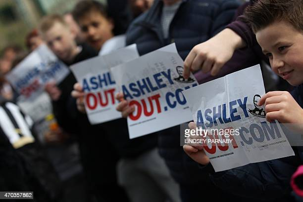 Newcastle fans boycotting the match holds signs demanding the resignation of owner Mike Ashley as club director before the English Premier League...