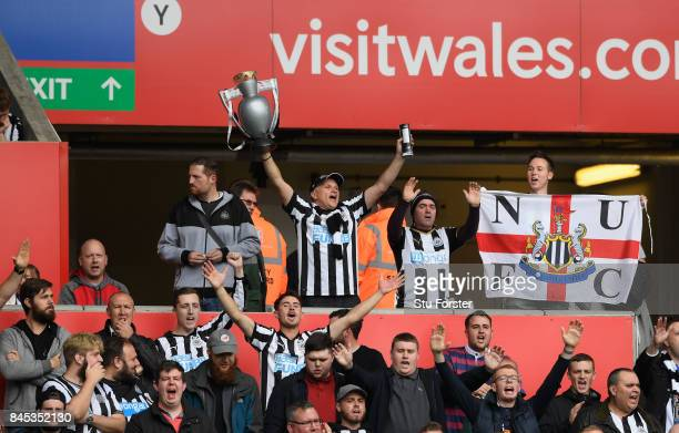 Newcastle fans with a replica Premier League trophy show their support during the Premier League match between Swansea City and Newcastle United at...