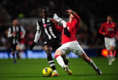 Newcastle forward Demba Ba is tackled by Phil Jones during the Barclays Premier league game between Newcastle United and Manchester United at St...
