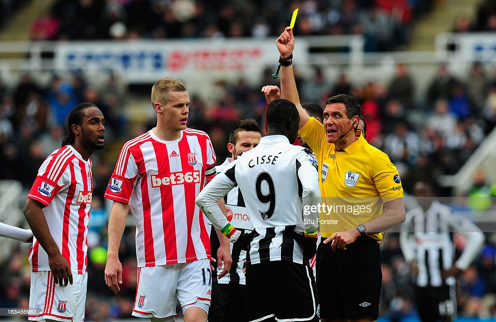 Newcastle forward Papiss Cisse is booked by referee <a gi-track='captionPersonalityLinkClicked' href=/galleries/search?phrase=Andre+Marriner&family=editorial&specificpeople=221003 ng-click='$event.stopPropagation()'>Andre Marriner</a> during the Barclays Premier League match between Newcastle United and Stoke City at St James' Park on March 10, 2013 in Newcastle upon Tyne, England.