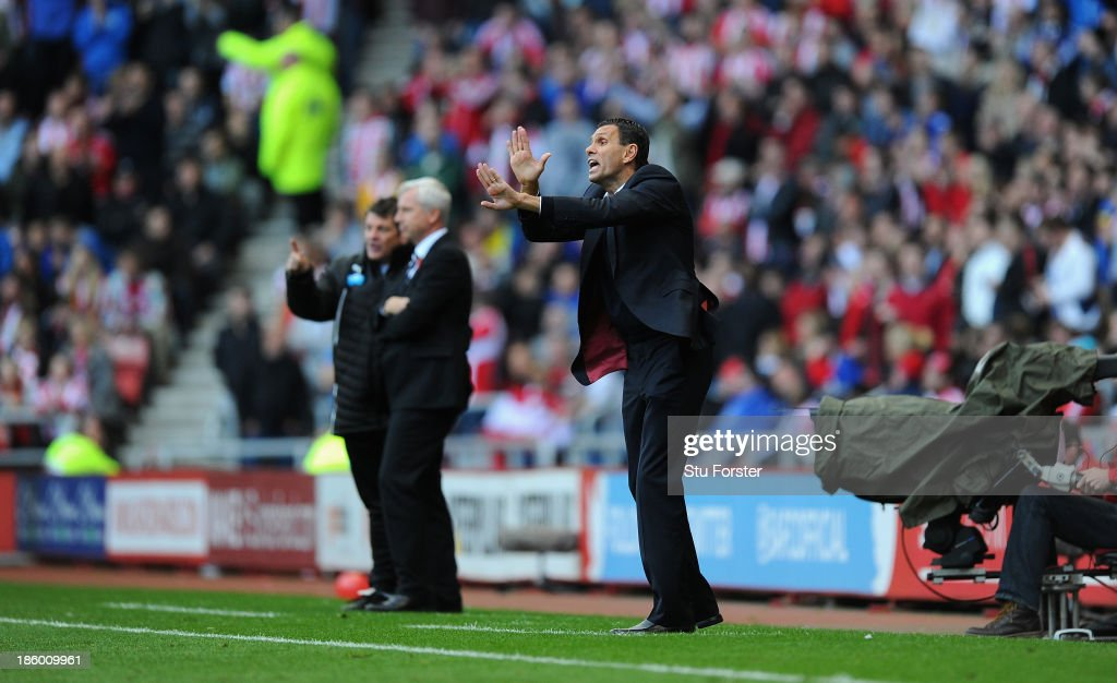 Newcastle manager Alan Pardew (l) looks on as Sunderland manager Gus Poyet reacts during the Barclays Premier League match between Sunderland and Newcastle United at Stadium of Light on October 27, 2013 in Sunderland, England.