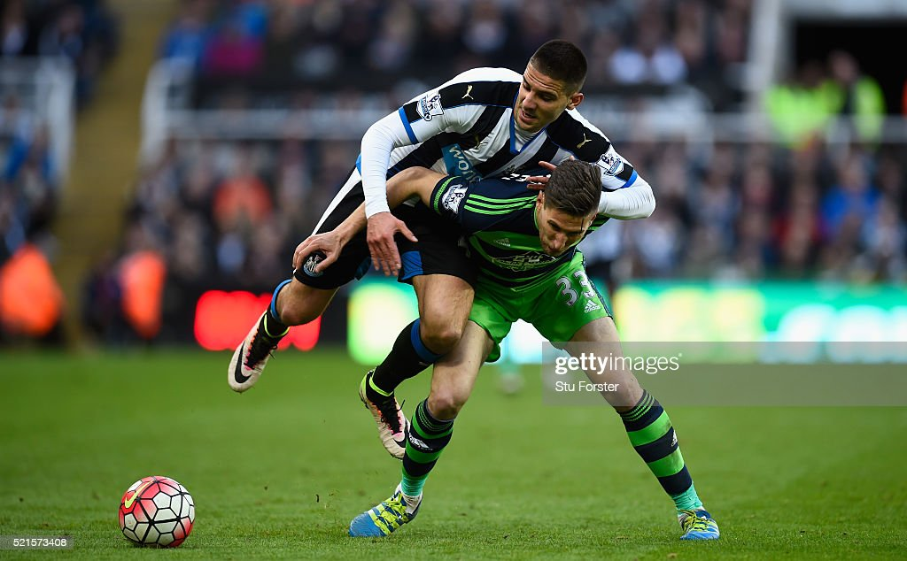 Newcastle player Aleksander Mitrovic races past Federico Fernandez of Swansea during the Barclays Premier League match between Newcastle United and Swansea City at St James' Park on April 16, 2016 in Newcastle Upon Tyne, England.