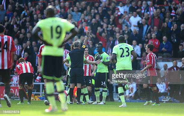 Newcastle player Cheick Tiote is shown the red card by referee Martin Atkinson during the Barclays Premier league match between Sunderland and...