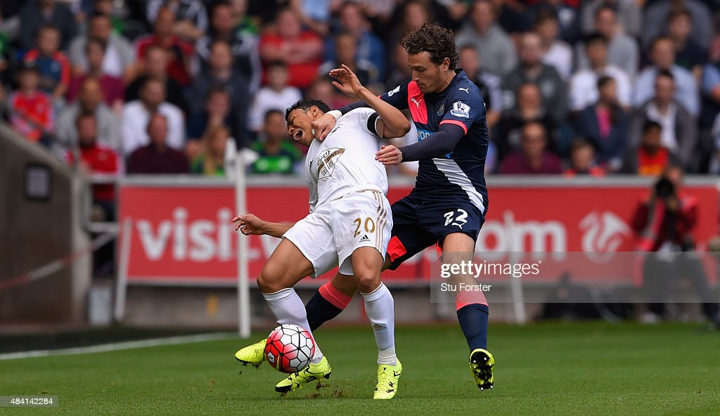 Newcastle player Daryl Janmaat (r) fouls Jefferson Montero of Swabnsea during the Barclays Premier League match between Swansea City and Newcastle United at the Liberty stadium on August 15, 2015 in Swansea, United Kingdom.
