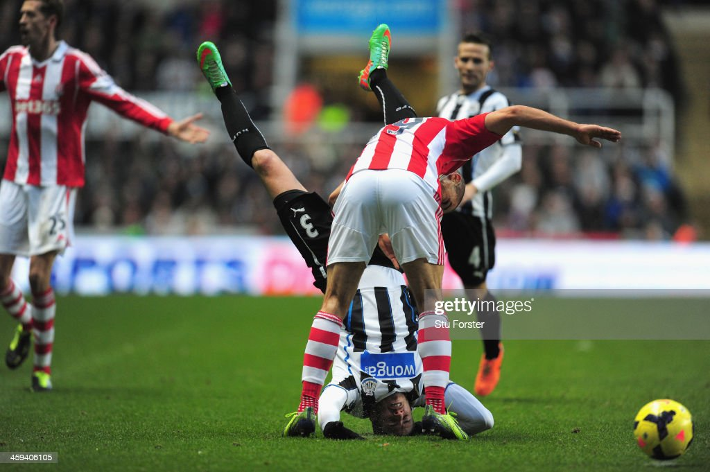 Newcastle player Davide Santon (upside down) is challenged by Jonathan Walters during the Barclays Premier League match between Newcastle United and Stoke City at St James' Park on December 26, 2013 in Newcastle upon Tyne, England.